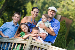 Portrait of a nice looking young family with four children happily posing outdoors.