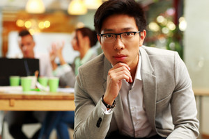 Portrait of a pensive asian man sitting in office