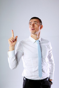 Portrait of a pensive businessman showing finger up on gray background