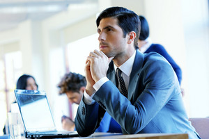 Portrait of a pensive businessman sitting at the table in office
