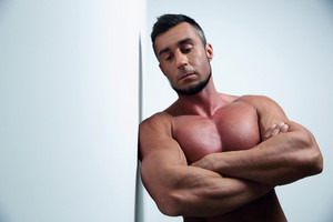 Portrait of a pensive muscular man with arms folded leaning on the wall