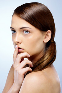 Portrait of a pensive woman holding a finger to her lips