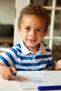 Portrait of a preschooler looking happy after finishing his homework
