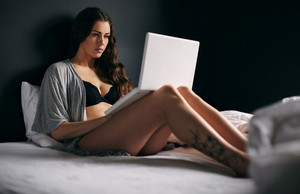Portrait of a pretty young woman wearing lingerie working on a laptop while sitting on bed. Attractive female model using laptop in bedroom.