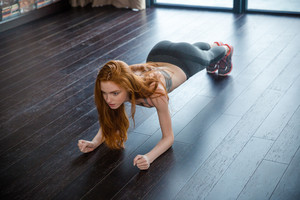 Portrait of a redhead fitness woman doing plank exercise