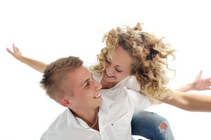 Portrait of a romantic young couple smiling together over white background
