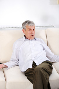 Portrait of a sad senior man sitting on sofa at home