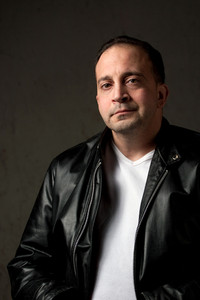 Portrait of a serious middle aged man in his upper 30s wearing a leather jacket in front of a grungy background.
