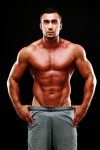 Portrait of a serious muscular man over black background