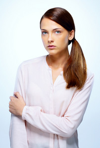 Portrait of a serious woman standing on blue background