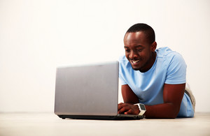 Portrait of a smiling african man lying on the floor and using laptop