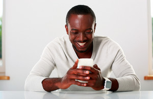 Portrait of a smiling african man using smartphone