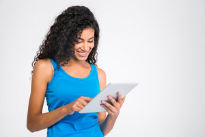 Portrait of a smiling afro american woman using tablet computer isolated on a white background