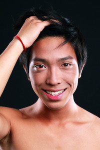 Portrait of a smiling asian man standing on black background