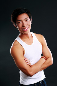 Portrait of a smiling asian man with arms folded on black background