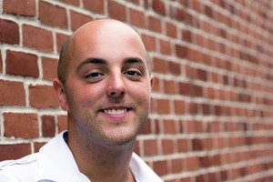 Portrait of a smiling bald young man posing in front of a brick wall.