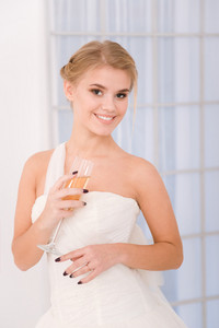 Portrait of a smiling bride holding glass with champagne
