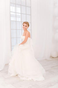 Portrait of a smiling bride standing in white wedding dress and looking at camera