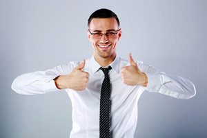 Portrait of a smiling businessman standing with thumbs up on gray background