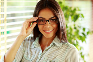 Portrait of a smiling businesswoman in glasses at office