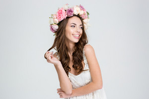 Portrait of a smiling cute woman with wreath of roses posing isolated on a white background