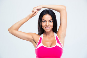 Portrait of a smiling fitness woman posing over gray background