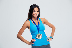 Portrait of a smiling fitness woman with medal standing over gray background. Looking at camera