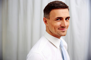 Portrait of a smiling handsome businessman in white shirt
