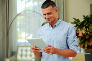 Portrait of a smiling man using tablet computer at home