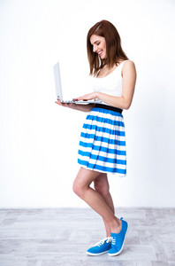 Portrait of a smiling woman standing and using laptop