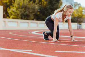 Portrait of a sports woman in star position for run on outdoor stadium