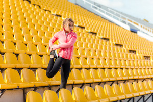 Portrait of a sports woman stretching legs at stadium