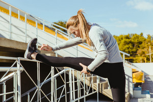 Portrait of a sports woman stretching legs outdoors