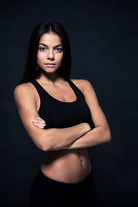 Portrait of a sports young woman standing with arms folded over black background