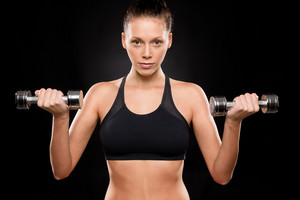 Portrait of a sporty woman lifting weights with both hands