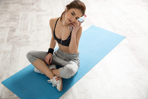 Portrait of a sporty woman sitting on the yoga mat with bottle of water
