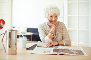 Portrait of a stylish old woman at home reading a magazine