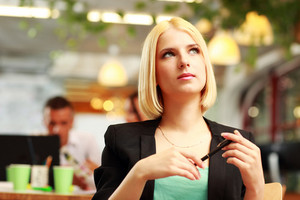 Portrait of a thoughtful blonde businesswoman looking up in office