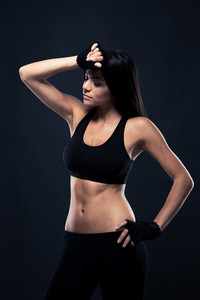 Portrait of a tired fitness woman standing over black background