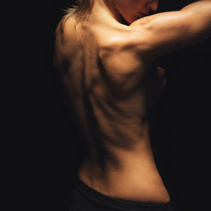 Portrait of a topless woman showing her back