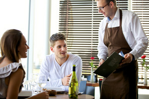 Portrait of a waiter taking the couple's order at a restaurant