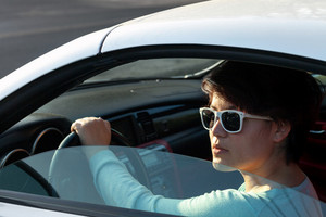 Portrait of a woman wearing sunglasses in a convertible sports car with the hard top up.