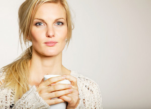 Portrait of a woman with unkept hair having her coffee in the morning