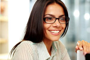 Portrait of a young cheerful businesswoman in glasses at office
