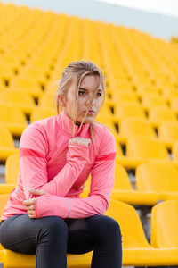 Portrait of a young fitness woman resting on outdoor stadium