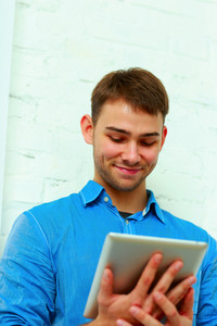 Portrait of a young hapiness businessman holding tablet computer and looking at it