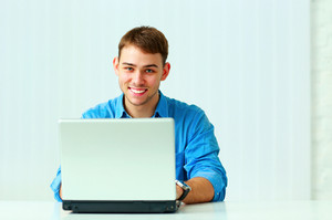 Portrait of a young happy businessman with laptop in office