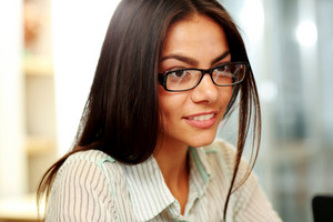 Portrait of a young happy businesswoman in glasses at office