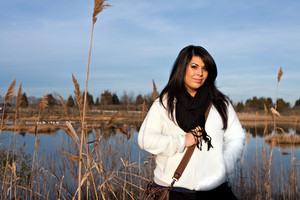 Portrait of a young Hispanic woman outdoors near a pond by the shoreline.