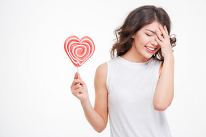 Portrait of a young laughing woman holding lollipop isolated on a white background